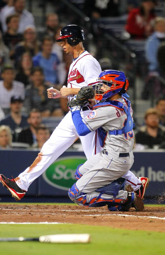 Atlanta Braves' Andrelton Simmons, top, is tagged out by New York Mets catcher Travis d'Arnaud at the plate in the fifth inning of a baseball game on Wednesday, April 9, 2014, in Atlanta