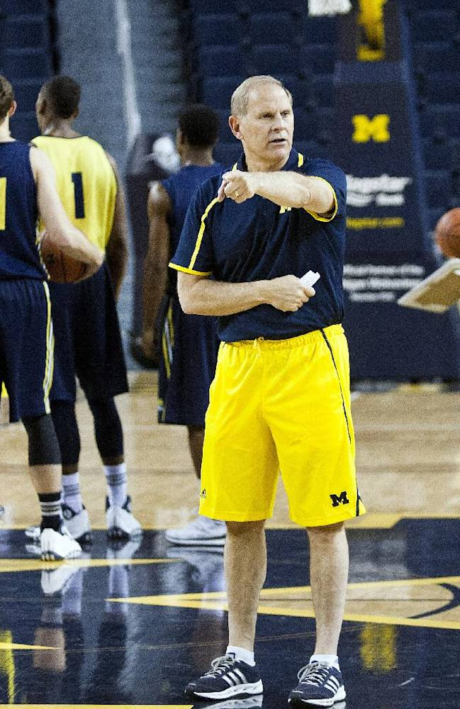 Michigan head coach John Beilein gives directions to his players on the court in a practice session during NCAA college basketball media day on Thursday, Oct. 24, 2013, in Ann Arbor, Mich