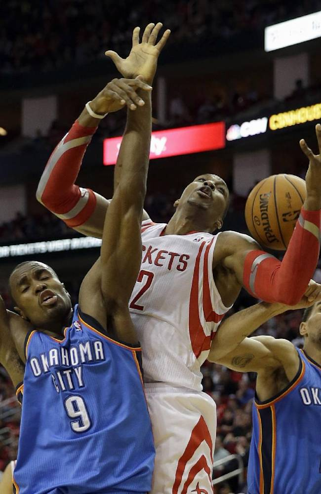 Houston Rockets' Dwight Howard (12) reaches for rebound with Oklahoma City Thunder's Serge Ibaka (9) and Thabo Sefolosha (25) during the third quarter of an NBA basketball game Thursday, Jan. 16, 2014, in Houston. The Thunder beat the Rockets 104-92