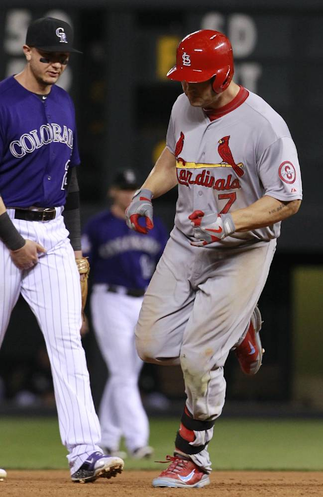 St. Louis Cardinals' Matt Holliday, right, circles the bases after his two-run home run as Colorado Rockies shortstop Troy Tulowitzki looks on in the fifth inning of the Cardinals' 11-4 victory in a baseball game in Denver on Tuesday, Sept. 17, 2013