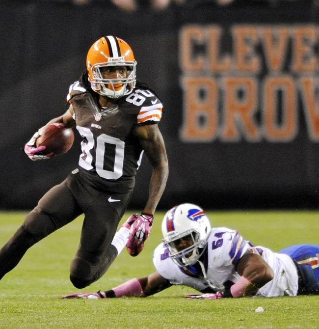 In this photo taken on Oct. 3, 2013, Cleveland Browns' Travis Benjamin (80) eludes Buffalo Bills' Marcus Dowtin on a punt return in the fourth quarter of an NFL football game in Cleveland. There's fast and then there's Benjamin, the Browns' fleet-footed punt returner who took one back 79 yards for a touchdown last week and earned his