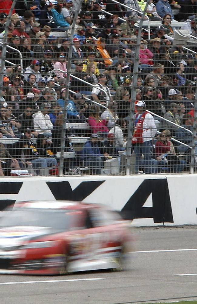In this Nov. 13, 2012 file photo, fans sit in the stands and watch the NASCAR Sprint Cup series auto race at Texas Motor Speedway in Fort Worth, Texas. Formula One boss Bernie Ecclestone  dismissed on Wednesday, Feb. 26, 2014, any clash between Formula One and NASCAR after the top executive at Texas Motor Speedway called F1