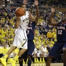 Michigan guard Trey Burke (3) passes the ball as Illinois' Brandon Paul (3) and Nnanna Egwu (32) defend during the second half of an NCAA college basketball game, Sunday, Feb. 24, 2013, in Ann Arbor, Mich. (AP Photo/Carlos Osorio)