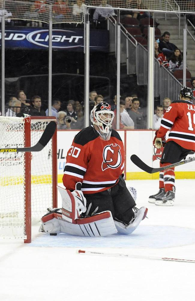 New Jersey Devils' Marek Zidlicky (2), goaltender Martin Brodeur (30), Travis Zajac (19) and Rostislav Olesz (25) react after New York Islanders' Josh Bailey (not shown) scored a goal during the first period of a preseason NHL hockey game, Thursday, Sept. 19, 2013, in Newark, N.J