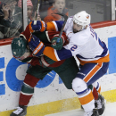 Minnesota Wild left wing Jason Zucker, left, and New York Islanders defenseman Nick Leddy, right, battle for the puck during the first period of an NHL hockey game in St. Paul, Minn., Tuesday, Dec. 9, 2014 The Associated Press