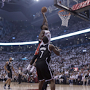Toronto Raptors' Amir Johnson shoots over Brooklyn Nets' Joe Johnson during the first half of Game 1 of an opening-round NBA basketball playoff series, in Toronto on Saturday, April 19, 2014 The Associated Press