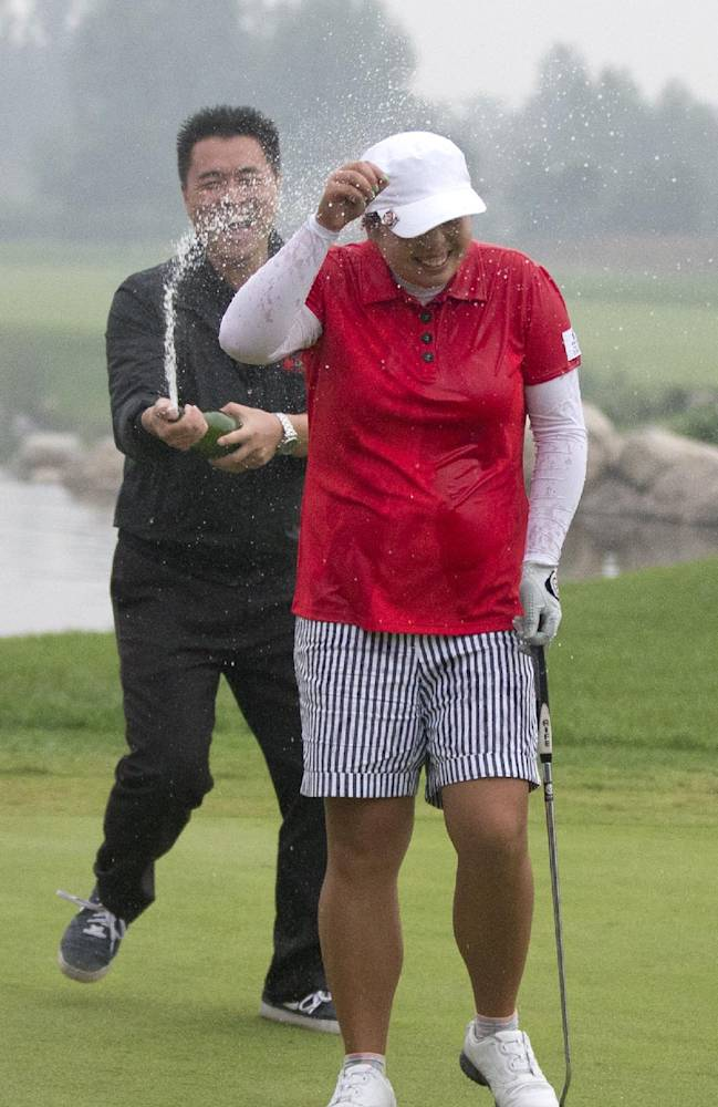 China's Feng Shanshan is showered with champagne by a man after her eagle shot on the 18th green to win the Reignwood LPGA Classic golf tournament at Pine Valley Golf Club on the outskirts of Beijing, China, Sunday, Oct. 6, 2013