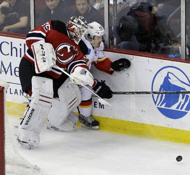 New Jersey Devils goalie Cory Schneider (35) checks Calgary Flames' Bryce Van Brabant (48) into the boards during the second period of an NHL hockey game in Newark, N.J., Monday, April 7, 2014
