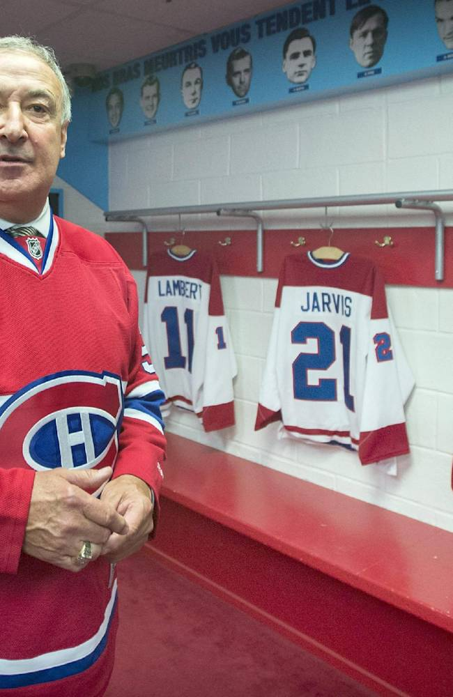 Former Montreal Canadiens' defenceman Guy Lapointe takes a look around a replica of his old locker room at the Canadiens' Hall of Fame in Montreal, Thursday, June 19, 2014, following a news conference announcing the retirement of his number 5 jersey