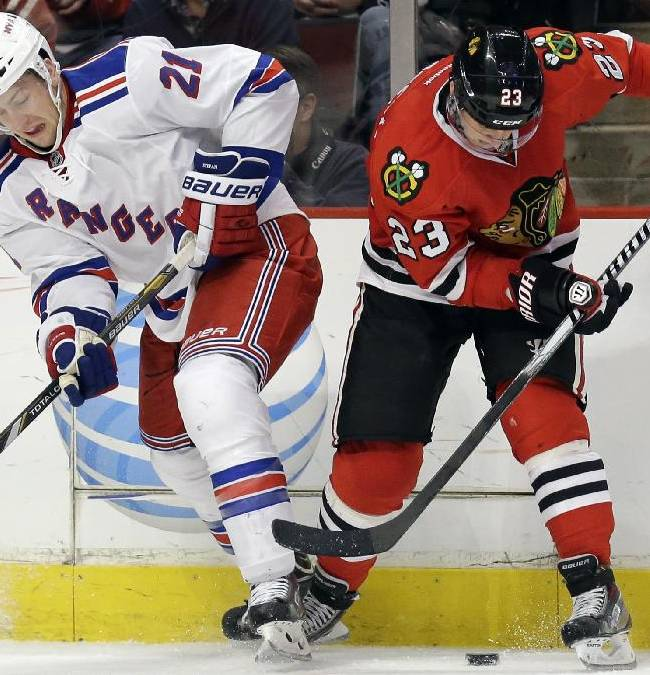 Chicago Blackhawks' Kris Versteeg, right, controls the puck against New York Rangers' Derek Stepan during the second period of an NHL hockey game in Chicago, Wednesday, Jan. 8, 2014