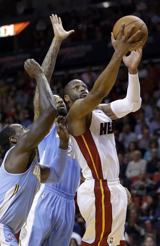 Miami Heat guard Dwyane Wade (3) prepares to shoot against Denver Nuggets forward Wilson Chandler (21) and J.J. Hickson, left, during the first  half of an NBA basketball game in Miami, Friday, March 14, 2014