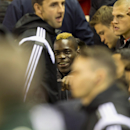 Liverpool's Mario Balotelli, centre, smiles as he sits on the substitutes bench, before the English League Cup soccer match between Liverpool and Swansea at Anfield Stadium, Liverpool, England, Tuesday Oct. 28, 2014
