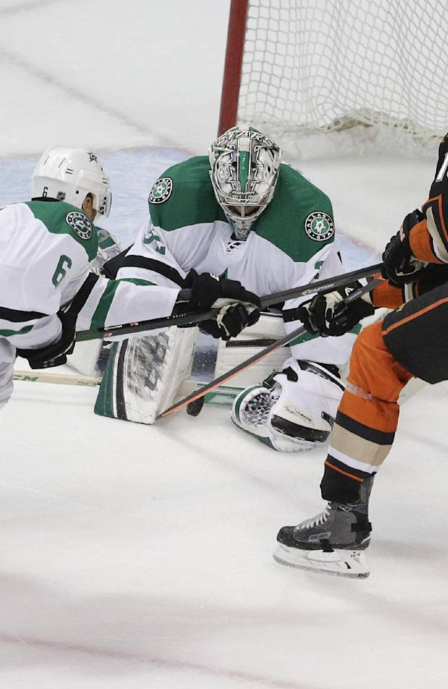 Dallas Stars' Kari Lehtonen, center, of Finland, stops a shot by Anaheim Ducks' Corey Perry, right, as Stars' Trevor Daley helps defend during the first period in Game 2 of the first-round NHL hockey Stanley Cup playoff series on Friday, April 18, 2014, in Anaheim, Calif