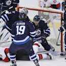 Winnipeg Jets' goaltender Ondrej Pavelec (31) loses track of Ottawa Senators' Milan Michalek's (9) shot as it slips past Jets Matt Halischuk (15), Jim Slater (19), Mark Stuart (5) and Ottawa Senators' Jason Spezza (19) during the first period of an NHL ho