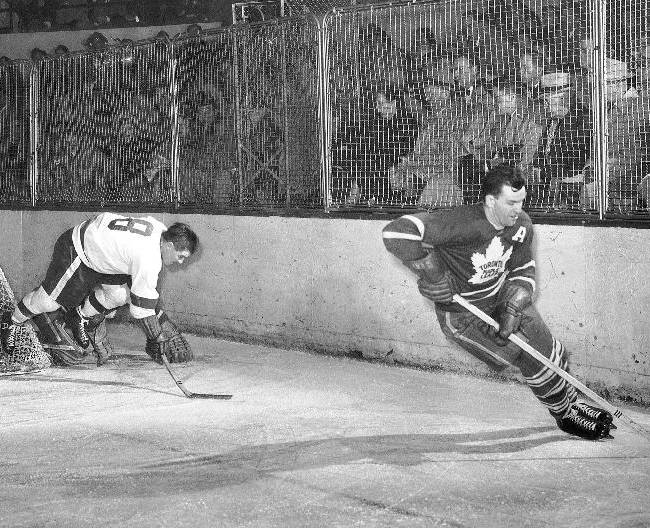 In this March 5, 1954, file photo, Toronto Maple Leaf's Tim Horton, right, outmaneuvers Detroit Red Wings' Tony Leswick (8) who falls to the ice during the first period of an NHL hockey game in Detroit. Few things unite Canadians the way Tim Hortons does. For half a century, they have warmed themselves on chilly mornings with the chain's coffee and Timbits  or doughnut holes to Americans. The chain's aura in Canada comes from its namesake: hockey Hall of Famer Tim Horton, the co-founder who died at 44 in a 1974 car accident after playing in a game for the Buffalo Sabres