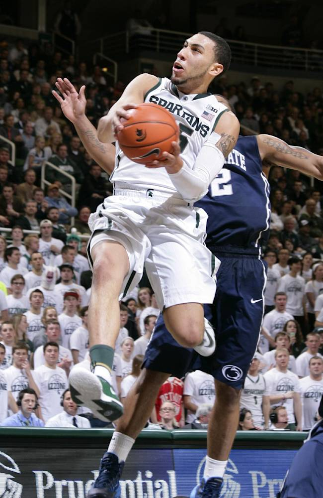 Michigan State's Denzel Valentine drives to the basket against Penn State's D.J. Newbill (2) and Tim Frazier, bottom, during the second half of an NCAA college basketball game Thursday, Feb. 6, 2014, in East Lansing, Mich. Michigan State won 82-67