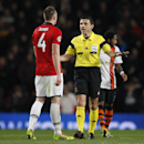 Manchester United's Phil Jones, left is spoken to by referee Milorad Mazic during their Champions League group A soccer match between Manchester United and Shakhtar Donetsk at Old Trafford Stadium, Manchester, England, Tuesday, Dec. 10, 2013