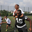 Oakland Raiders Marcel Reece plays football with children during an event in Guildford, England, Tuesday, Sept. 23, 2014. The Raiders will play the Miami Dolphins in an NFL football game at London's Wembley Stadium on Sunday Sept. 28. The Associated Press
