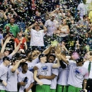 Oregon players hold up the championship trophy after defeating UCLA in an NCAA college basketball game at the Pac-12 Conference tournament, Saturday, March 16, 2013, in Las Vegas. Oregon won 78-69. (AP Photo/Julie Jacobson)