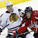 Chicago Blackhawks defenseman Sheldon Brookbank (17) and Washington Capitals center Jay Beagle (83) keep their eye on the puck in the third period of an NHL hockey game, Friday, April 11, 2014, in Washington. Beagle had two goals. The Capitals won 4-0 The