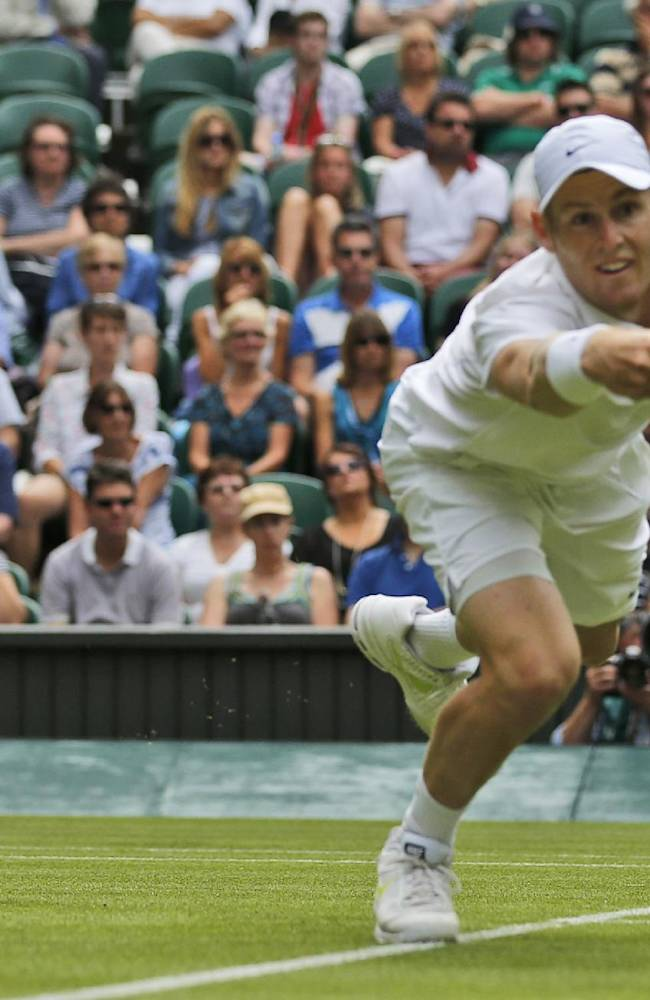 Luke Saville of Australia dives to play a return to Grigor Dimitrov of Bulgaria during their men's singles match at the All England Lawn Tennis Championships in Wimbledon, London, Wednesday, June 25, 2014