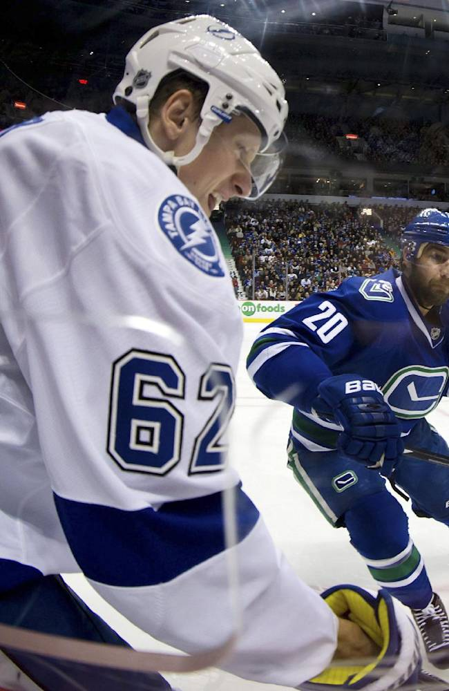 Vancouver Canucks' Chris Higgins, right, skates in to check Tampa Bay Lightning's Andrej Sustr, of the Czech Republic, during the first period of an NHL hockey game in Vancouver, British Columbia, on Wednesday, Jan. 1, 2014