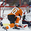 Washington Capitals' Justin Peters, right, and Steve Oleksy, left, cannot stop a goal by Philadelphia Flyers' Jakub Voracek as Vincent Lecavalier, center, pressures during the first period of a preseason NHL hockey game, Monday, Sept. 22, 2014, in Philad