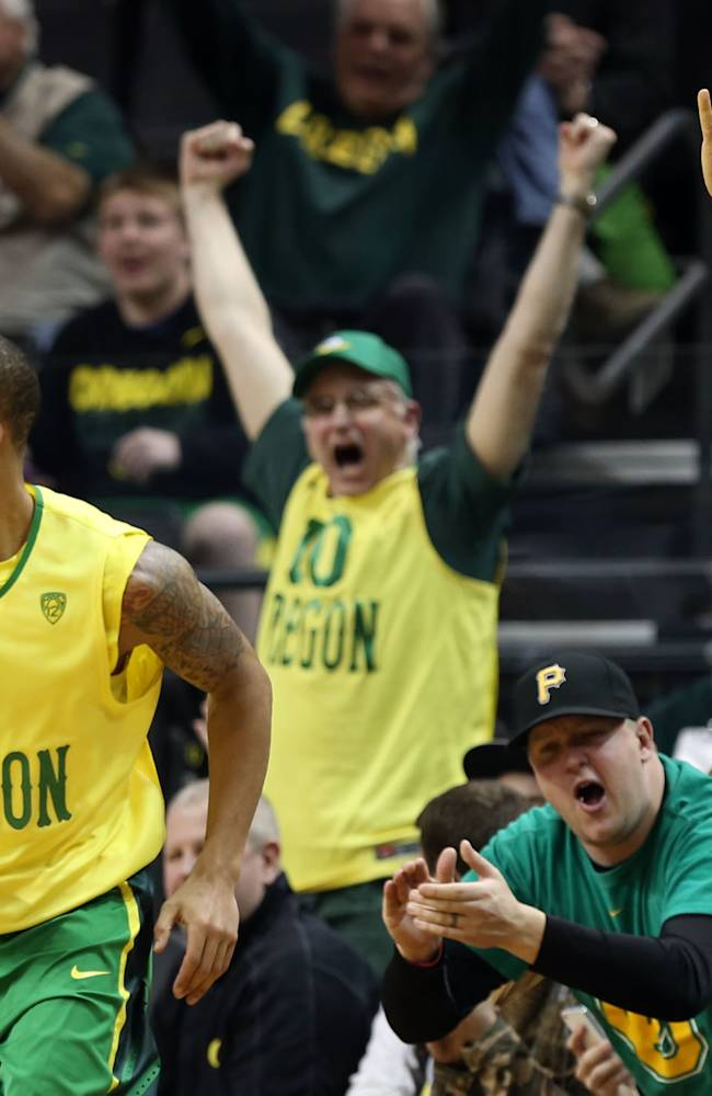 Oregon's Joseph Young, left, runs down court after sinking a 3-point shot against Washington State as fans cheer late in the second half of an NCAA college basketball game in Eugene, Ore., Sunday, Feb. 23, 2014