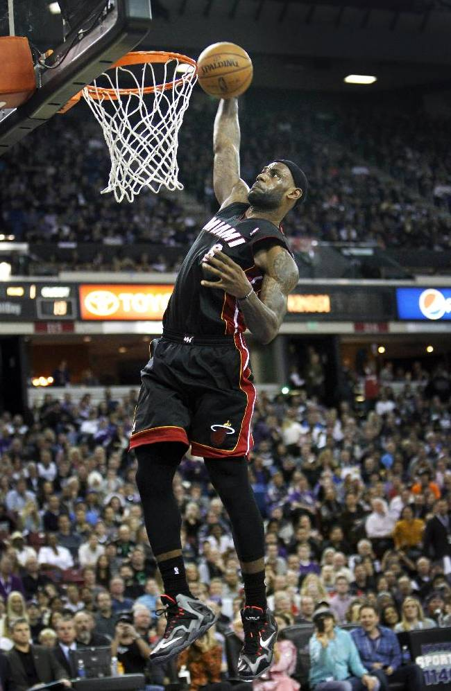 Miami Heat forward LeBron James dunks after a breakaway against the Sacramento Kings during the first half of an NBA basketball game in Sacramento, Calif., on Friday, Dec. 27, 2013