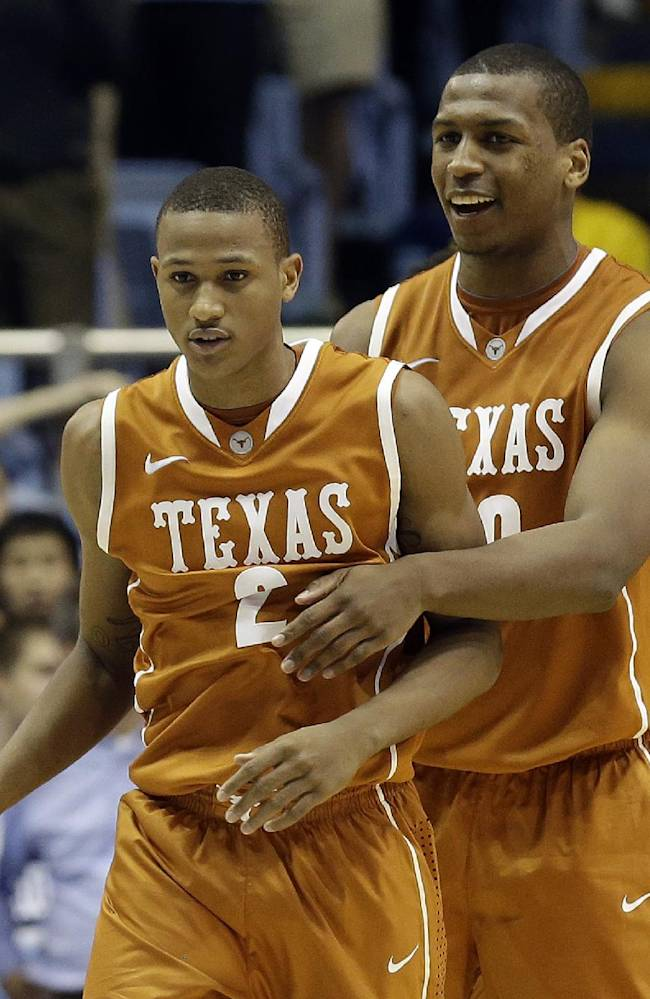Texas' Demarcus Holland, front, and Jonathan Holmes celebrate near the end of Texas' 86-83 win over North Carolina in an NCAA college basketball game in Chapel Hill, N.C., Wednesday, Dec. 18, 2013