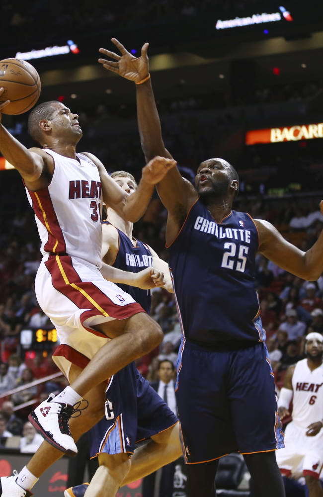 Charlotte Bobcats players Cody Zeller (40) and Al Jefferson (25) try to block Miami Heat's Shane Battier (31) during the first half of an NBA basketball game in Miami, Monday, March 3, 2014