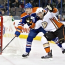 Anaheim Ducks' Patrick Maroon (19) and Edmonton Oilers' Brandon Davidson (88) battle for the puck as goalie Viktor Fasth (35) looks for the rebound during the first period of their NHL hockey game in Edmonton, Alberta, Canada on Friday, Dec. 12, 2014 The
