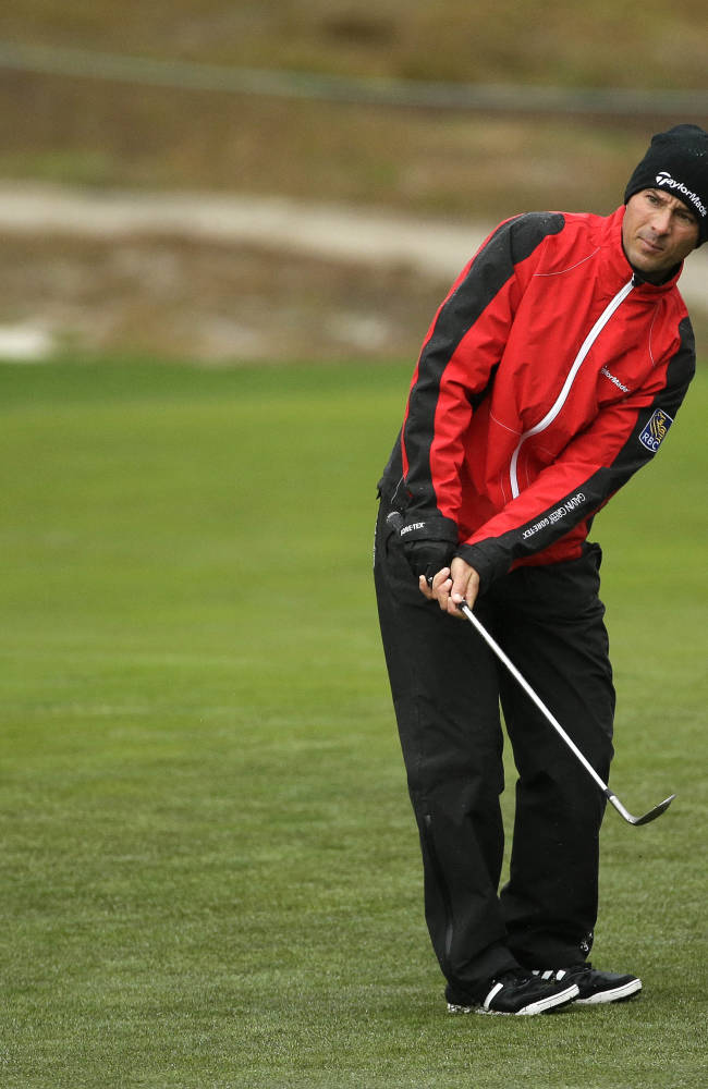 Mike Weir of Canada chips the ball up to the 10th green of the Monterey Peninsula Country Club Shore Course during the first round of the AT&T Pebble Beach Pro-Am golf tournament Thursday, Feb. 6, 2014, in Pebble Beach, Calif. Play was suspended because of steady rain