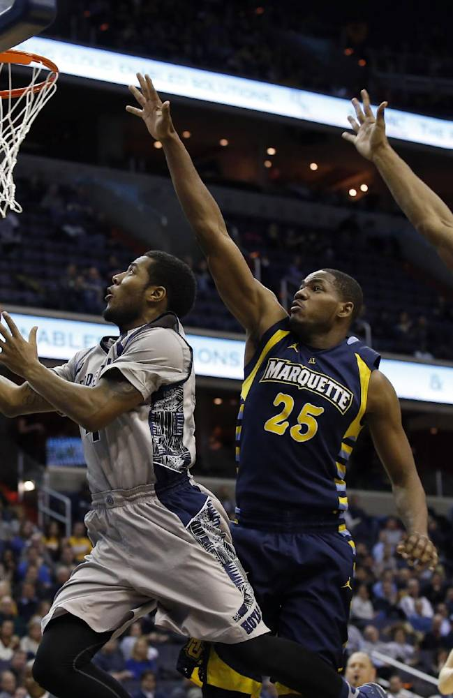 Georgetown guard D'Vauntes Smith-Rivera (4) shoots past Marquette forward Steve Taylor, Jr. (25) and guard John Dawson (2) during the second half of an NCAA college basketball game, Monday, Jan. 20, 2014, in Washington. Smith-Rivera had 24 points, but Marquette won 80-72 in overtime