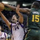 Utah Jazz forward Derrick Favors (15) fouls Phoenix Suns forward Luis Scola, of Argentina, during the first half of an NBA ba