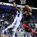 Louisville guard Russ Smith (2) shoots against Seton Hall's Fuquan Edwin during the first half of an NCAA college basketball game, Wednesday, Jan. 9, 2013, in Newark, N.J. (AP Photo/Julio Cortez)
