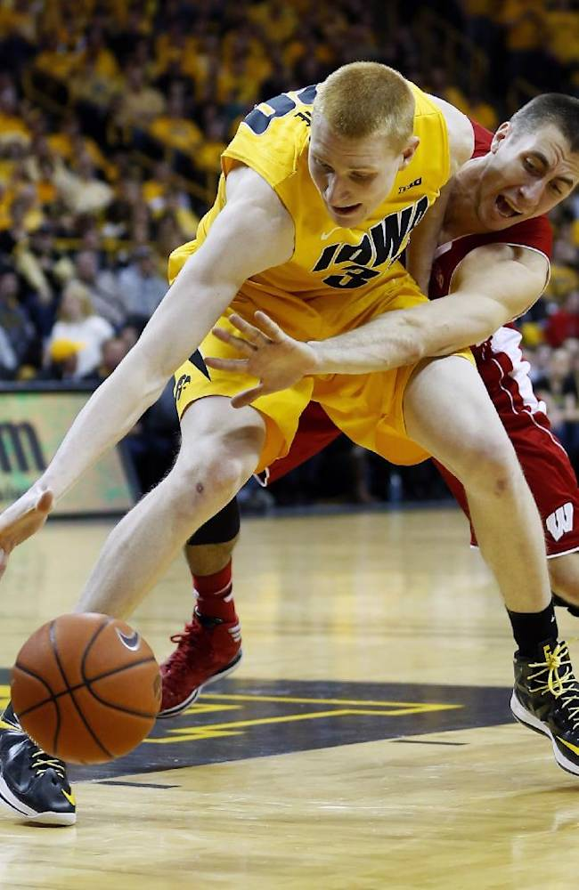 Wisconsin guard Josh Gasser knocks the ball away from Iowa forward Aaron White during the second half of an NCAA college basketball game in Iowa City, Iowa, Saturday, Feb. 22, 2014. Wisconsin won 79-74