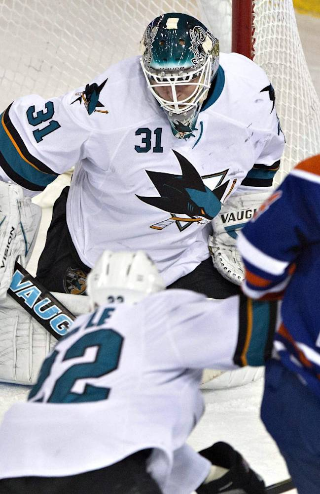San Jose Sharks goalie Antti Niemi (31) makes the save on Edmonton Oilers Jordan Eberle (14) as Dan Boyle (22) defends during the second period of an NHL hockey game Wednesday, Jan. 29, 2014, in Edmonton, Alberta