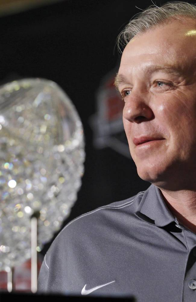 Florida State head coach Jimbo Fisher poses with The Coaches' Trophy during a news conference for the BCS National Championship NCAA college football game Tuesday, Jan. 7, 2014, in Newport Beach, Calif. Florida State beat Auburn 34-31 to win the championship the night before
