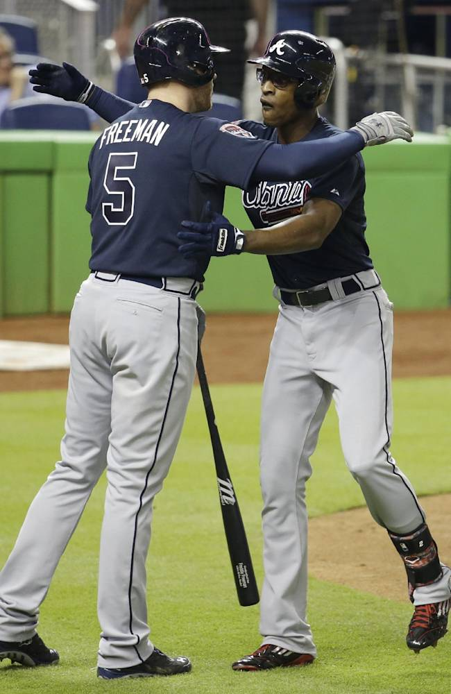 Atlanta Braves' B.J. Upton, right, is met by Freddie Freeman (5) at the plate after hitting a three-run home run in the third inning of a baseball game against the Miami Marlins, Thursday, May 1, 2014, in Miami