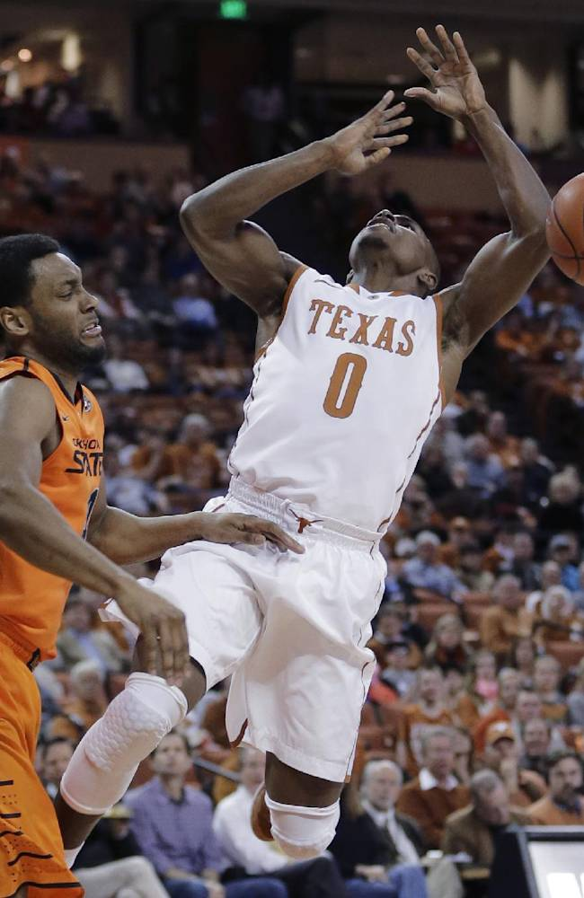 Oklahoma State's Brian Williams, left, knocks the ball away from Texas' Kendal Yancy (0) during the first half on an NCAA college basketball game, Tuesday,  Feb. 11, 2014, in Austin, Texas