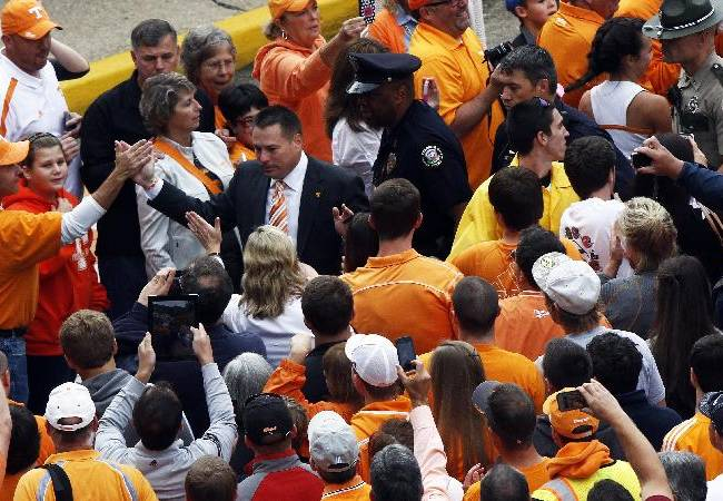 Tennessee head coach Butch Jones makes his way through fans during the Vol Walk before an NCAA college football game against South Carolina on Saturday, Oct. 19, 2013 in Knoxville, Tenn