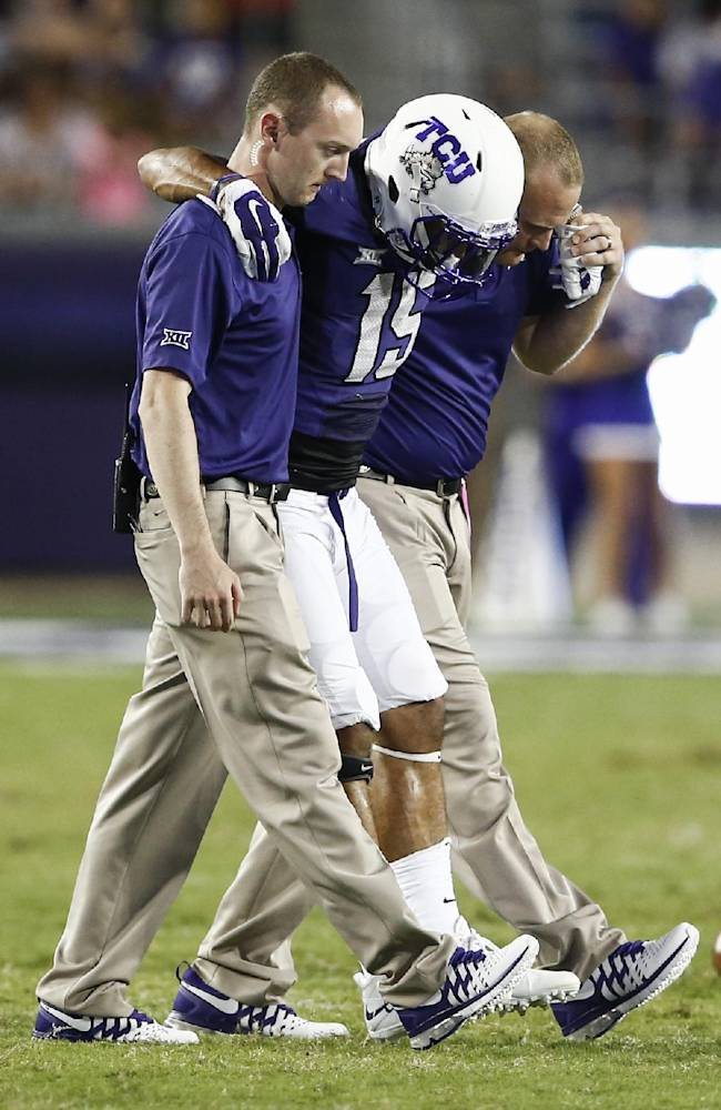 TCU wide receiver Cameron Echols-Luper (15) is assisted off the field by team trainers after an injury on a punt return against Samford in the second half of an NCAA college football game in Fort Worth, Texas, Saturday, Aug. 30, 2014. TCU won 48-14