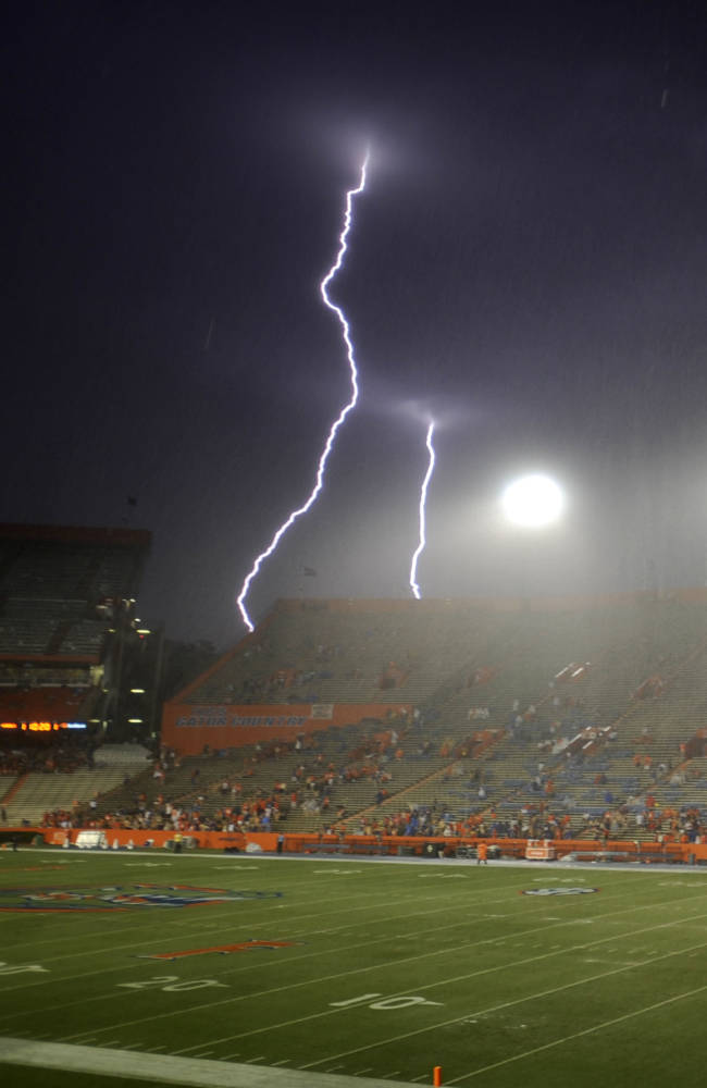 Lightning strikes near Ben Hill Griffin Stadium at Florida Field during a weather delay before an NCAA college football game between Florida and Idaho in Gainesville, Fla., Saturday, Aug. 30, 2014