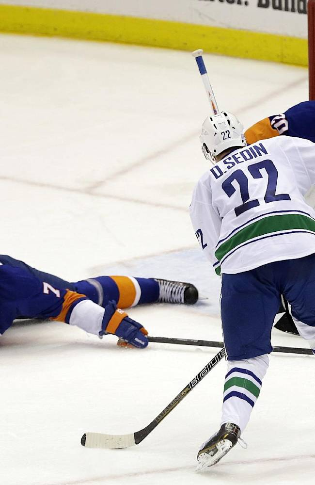 Vancouver Canucks' Daniel Sedin (22) shoots the puck as New York Islanders goalie Evgeni Nabokov (20) and Matt Carkner (7) defend during the second period of an NHL hockey game Tuesday, Oct. 22, 2013 in Uniondale, N.Y. Sedin would score on the play