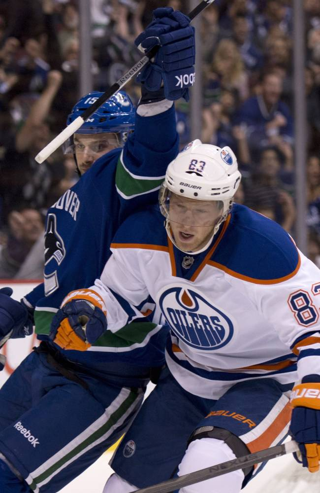 Vancouver Canucks center Brad Richardson (15) celebrates his goal as Edmonton Oilers right wing Ales Hemsky (83) skates past during the first period of an NHL hockey game in Vancouver, British Columbia, Saturday, Oct. 5, 2013