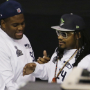 Seattle Seahawks' Marshawn Lynch, right, talks to teammate Brandon Mebane as he makes his way out off the floor at the beginning of media day for NFL Super Bowl XLIX football game Tuesday, Jan. 27, 2015, in Phoenix. (AP Photo/Charlie Riedel)
