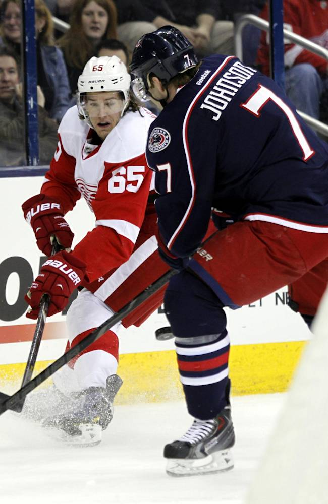 Detroit Red Wings' Danny DeKeyser, left, works for the puck against Columbus Blue Jackets' Jack Johnson in the first period of an NHL hockey game in Columbus, Ohio, Tuesday, March 11, 2014