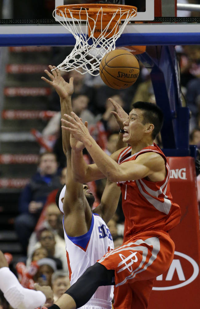Houston Rockets' Jeremy Lin, right, cannot hang on to the ball as Philadelphia 76ers' Brandon Davies defends during the second period of an NBA basketball game, Wednesday, Nov. 13, 2013, in Philadelphia. Philadelphia won 123-117 in overtime
