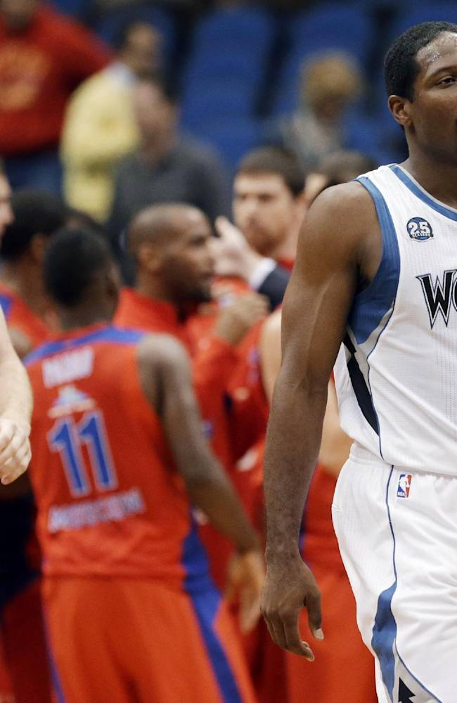 Minnesota Timberwolves' Robbie Hummel, left, and Othyus Jeffers leave the floor as CSKA Moscow players celebrate after defeating the  Timberwolves 108-106 in overtime in an exhibition NBA basketball game, Monday, Oct. 7, 2013, in Minneapolis